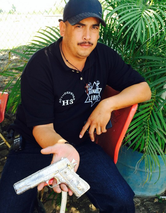 """BUENA VISTA, MEXICO--January 17, 2013: Luis Antonio Torres Gonzalez, known as """"El Americano"""", a leader of the militia movement, shows off a pistol he says was confiscated from the Knights Templar drug gang."""