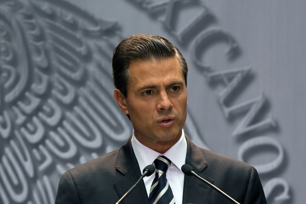 "Enrique Pena Nieto, Mexico's president, speaks about the killing of students in Iguala, Mexico, during remarks at the National Palace in Mexico City, Mexico, on Monday, Oct. 6, 2014. Gang members acting in concert with local police allegedly killed 17 college students following a clash just over a week ago, according to a state prosecutor. Pena Nieto condemned the deaths as ""painful and unacceptable"" and vowed to bring the perpetrators to justice. Photographer: Susana Gonzalez/Bloomberg via Getty Images"