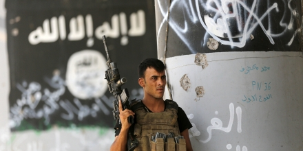 "A member of Iraqi counterterrorism forces stands guard near Islamic State militant graffiti in Fallujah, Iraq, Monday, June 27, 2016. Thick clouds of black smoke billowed over northwest Fallujah Monday as dozens of homes continued to burn a day after the city was declared ""fully liberated"" from the Islamic State group. Iraqi special forces Lt. Gen. Abdel Wahab al-Saadi who led the operation to retake the city, said that IS militants torched hundreds of houses in Fallujah's north and west as they fled Sunday, just as the fighters did in many of the city's other neighborhoods over the course of the operation. (AP Photo/Hadi Mizban)"