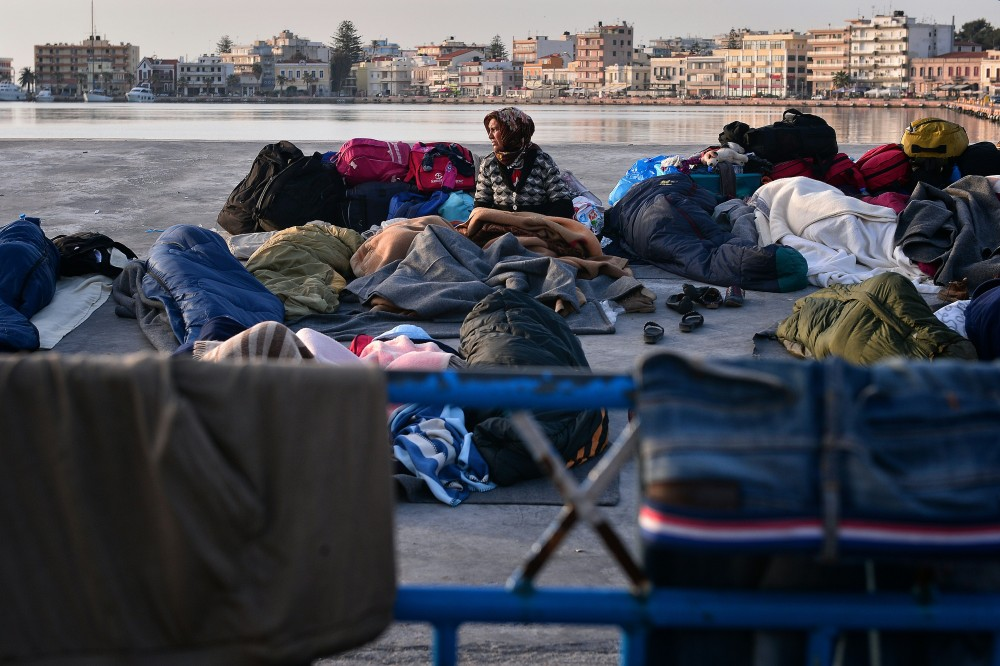 """A woman wakes up in the port of Chios, where refugees and migrants who managed to leave the VIAL detention center a few days ago are camping out on April 5, 2016.<br /><br /><br /><br /><br /><br /><br /><br /><br /><br /><br /><br /><br /><br /><br /><br /> Greece sent a first wave of migrants back to Turkey on April 4 under an EU deal that has faced heavy criticism from rights groups. Under the agreement, designed to halt the main influx which comes from Turkey, all """"irregular migrants"""" arriving since March 20 face being sent back, although the deal calls for each case to be examined individually. For every Syrian refugee returned, another Syrian refugee will be resettled from Turkey to the EU, with numbers capped at 72,000.  / AFP / LOUISA GOULIAMAKI        (Photo credit should read LOUISA GOULIAMAKI/AFP/Getty Images)"""