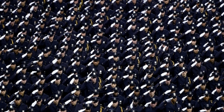 Graduating officers with the  New York Police Department 2016  graduation class salute during a ceremony at Madison Square Garden July, 1, 2016. / AFP / TIMOTHY A. CLARY        (Photo credit should read TIMOTHY A. CLARY/AFP/Getty Images)