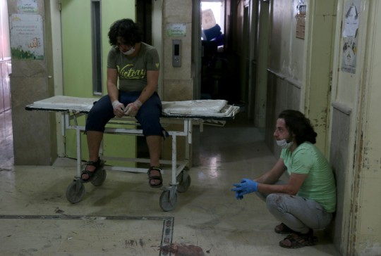 Hospital workers react after a barrel bomb struck just outside the Omar bin Abdaziz hospital in the Maadi district of the northern Syrian city of Aleppo following government air raids on rebel-held districts of the city on July 16, 2016. Air raids on rebel-held districts of Syria's battleground second city of Aleppo killed at least 21 civilians including children, the Syrian Observatory for Human Rights said. / AFP / THAER MOHAMMED (Photo credit should read THAER MOHAMMED/AFP/Getty Images)
