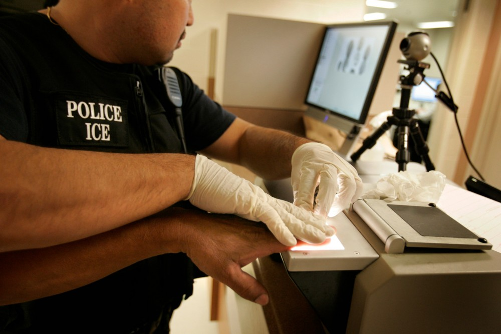 An Immigration and Customs Enforcement (ICE) Fugitive Operations Team member fingerprints a man (both faces and identity must be concealed) who was convicted of domestic violence and vehicle theft, at the ICE Santa Ana Staging Facility in Santa Ana recently. The man was then scheduled to be deported to Guatemala. ICE is doing its biggest ever fugitive operation, where agents pick up people who have already been deported or are criminal aliens . Photos taken Sept. 27, 2007 in Santa Ana. More than 1,300 illegal immigrants were arrested during the operation. 530 of the arrestees were taken from the streets.  (Photo by Allen J. Schaben/Los Angeles Times via Getty Images)