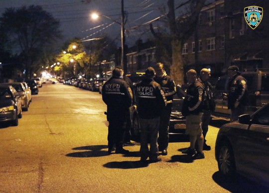 In this photo provided by the New York City Police Department, officers gather at a location in the Bronx borough of New York during a takedown of two rival drug gangs in the early hours of Wednesday, April 27, 2016. According to the U.S. Attorney, nearly 700 New York Police Department officers and federal agents accompanied by helicopters and armored trucks executed pre-dawn raids, taking down the rival drug gangs from top to bottom. (New York Police Department via AP)