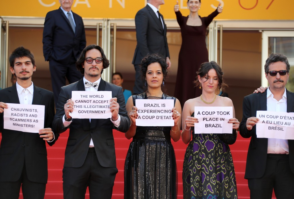 """(FromL) Brazilian actor Pedro Queiroz, Brazilian actor Allan Souza, Brazilian actress Maeve Jinkings, French-Brazilian producer Emilie Lesclaux and Brazilian director Kleber Mendonca Filho hold protest signs as they arrive on May 17, 2016 for the screening of the film """"Aquarius"""" at the 69th Cannes Film Festival in Cannes, southern France.  / AFP / Valery HACHE        (Photo credit should read VALERY HACHE/AFP/Getty Images)"""