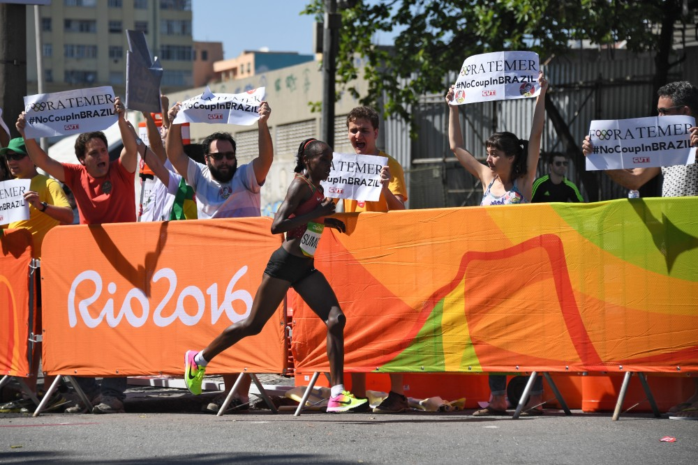 """RIO DE JANEIRO, BRAZIL - AUGUST 14:  Kenya's Jemima Jelagat Sumgong runs past protester holding banner against Brazil's interim leader reading """"Fora Temer"""" (Temer out) in the finish area of the Women's Marathon during the athletics event at the Rio 2016 Olympic Games at Sambodromo in Rio de Janeiro on August 14, 2016.    (Photo by Johannes EISELE-Pool/Getty Images)"""