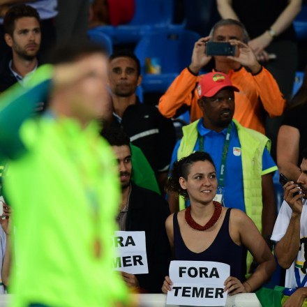 """Gold medallist Brazil's Thiago Braz Da Silva (L) celebrates on the podium as people hold a banner reading """"out with Temer"""" (Brazil's interim president Michel Temer) at the medal ceremony for the men's pole vault during the athletics event at the Rio 2016 Olympic Games at the Olympic Stadium in Rio de Janeiro on August 16, 2016. / AFP / FRANCK FIFE        (Photo credit should read FRANCK FIFE/AFP/Getty Images)"""