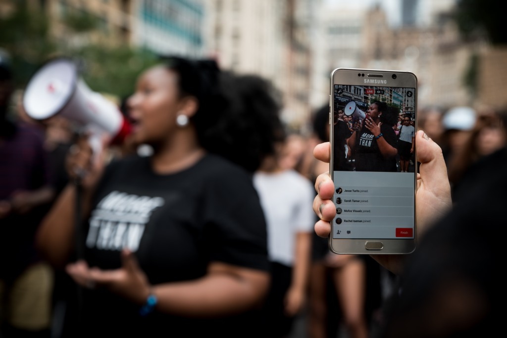 A demonstrator live streams the march on Facebook Sunday in Union Square. Following several police involved shootings of black men throughout America, hundreds of emotionally effected people turned to the streets to demonstrate and fight for change.  Demonstrators marched from Times Square to Union Square in New York City on July 10, 2016. (Monica Jorge) *** Please Use Credit from Credit Field ***