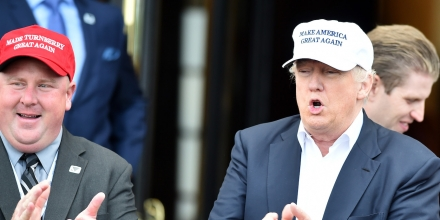 AYR, SCOTLAND - JUNE 24:  A supporter in a red hat stands next to Presumptive Republican nominee for US president Donald Trump as he arrives to his Trump Turnberry Resort on June 24, 2016 in Ayr, Scotland. Mr Trump arrived to officially open his golf resort which has undergone an eight month refurbishment as part of an investment thought to be worth in the region of two hundred million pounds.  (Photo by Jeff J Mitchell/Getty Images)