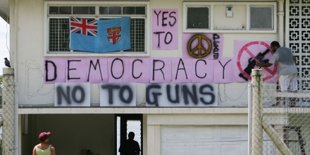 SUVA, FIJI - DECEMBER 02:  Local resident Tony Qumi paints a protest sign on the front of his house after the proposed military coup deadline passes December 2, 2006 in Suva, Fiji. Fiji's Prime Minister Laisenia Qarase is in hiding while its military commander, Frank Bainimarama, has not acted on threats to launch a