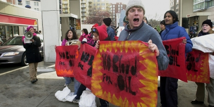 WASHINGTON, :  Activists stage a protest 04 December, 2002 at an Exxon gas station in Washington, DC to highlight the role of the oil industry in pushing for a US invasion of Iraq. The demonstrators, chanting