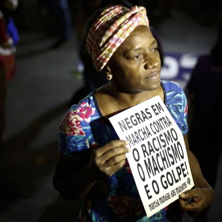 """A woman holds a sign reading """"Black women march against racism, male chauvinism and the coup"""" during a protest against the president of the Brazilian lower house Eduardo Cunha, Brazilian Vice-President Michel Temer and Jair Bolsonaro -a far right member of Congress who has praised Brazil's former military dictatorship and torture of opponents in the 1970s- in Sao Paulo, Brazil on April 26, 2016. Six out of 10 Brazilians want snap elections to resolve the country's political crisis in which leftist President Dilma Rousseff faces impeachment, a poll released Tuesday said. / AFP / Miguel Schincariol        (Photo credit should read MIGUEL SCHINCARIOL/AFP/Getty Images)"""