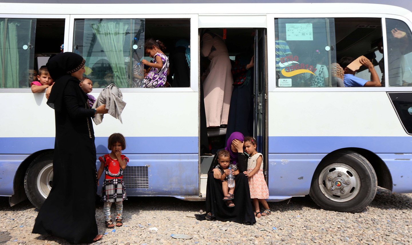 Iraqi families who had fled the violence around the northern Iraqi city of Mosul, board a bus in the Dibaga camp in the town of Makhmur, before returning to their villages south of the city of Mosul on September 1, 2016.  / AFP / SAFIN HAMED        (Photo credit should read SAFIN HAMED/AFP/Getty Images)