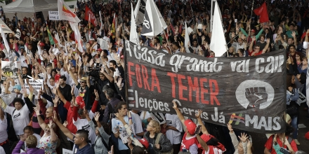 Demonstrators holding a banner that reads in Portuguese