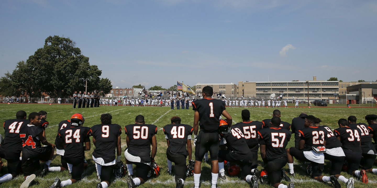 Woodrow Wilson High's Edwin Lopez (#1) stands while some of his teammates kneel during the national anthem before Woodrow Wilson High School played Highland High School at Woodrow Wilson High School in Camden, N.J., Saturday, Sept. 10, 2016. Colin Kaepernick's protest against social injustices has opened discussion and debate on a national level. For high schools across the country, where a host of football players have joined the San Francisco quarterback by kneeling during the national anthem, the issue is much more personal and complicated. (Yong Kim/The Philadelphia Inquirer via AP)