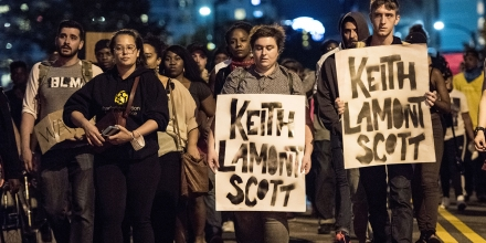 CHARLOTTE, NC - SEPTEMBER 22: Demonstrators march during protests September 22, 2016 in Charlotte, North Carolina. Protests began on Tuesday night following the fatal shooting of 43-year-old Keith Lamont Scott at an apartment complex near UNC Charlotte. A state of emergency was declared overnight in Charlotte and a midnight curfew was imposed by mayor Jennifer Roberts, to be lifted at 6 a.m. (Photo by Sean Rayford/Getty Images)
