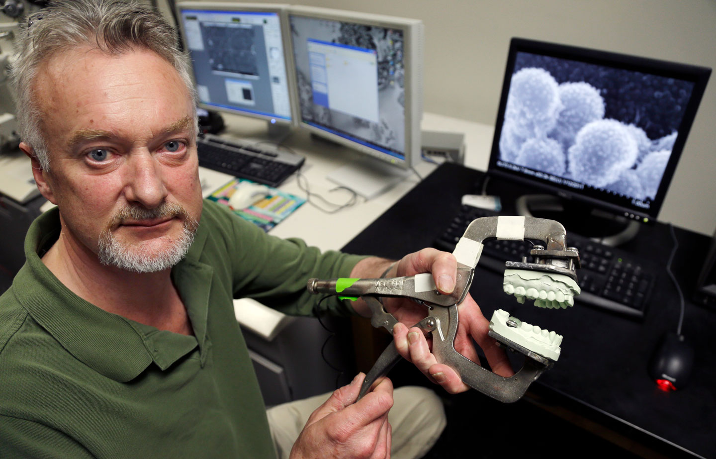 In this April 17, 2013 photo, Peter Bush, Research Scientist at the University at Buffalo, poses for a photo with a modified Vise-Grip tool attached to a dental mold that is used for test bites in skin at the school in Buffalo, N.Y.  Bite marks, long accepted as criminal evidence, now face doubts about reliability. (AP Photo/David Duprey)