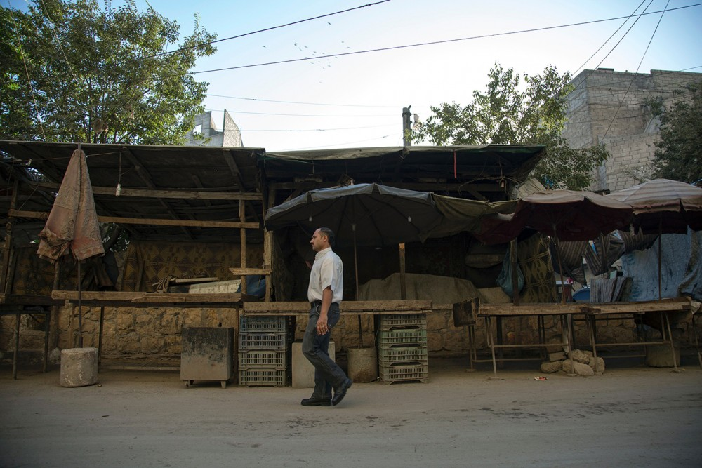 A Syrian man walks past an empty vegetable market in Aleppo on July 10, 2016, after the regime closed the only remaining supply route into the city.