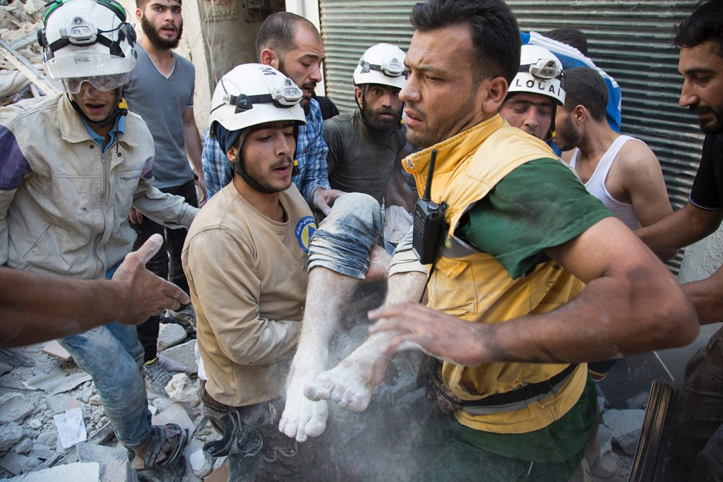 Syrian civil defense volunteers, known as the White Helmets, carry a body after digging it out from under the rubble of a building following a reported airstrike in the northern city of Aleppo on July 23, 2016.