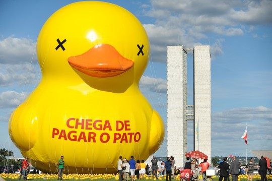 "The Federation of Industries of the State of Sao Paulo (FIESP) protest with a giant duck against taxes with a giant duck with an inscription that reads ""Enough of taking the blame"" at the Esplanada dos Ministérios in Brasilia on March 29, 2016. AFP PHOTO/ANDRESSA ANHOLETE / AFP / Andressa Anholete        (Photo credit should read ANDRESSA ANHOLETE/AFP/Getty Images)"