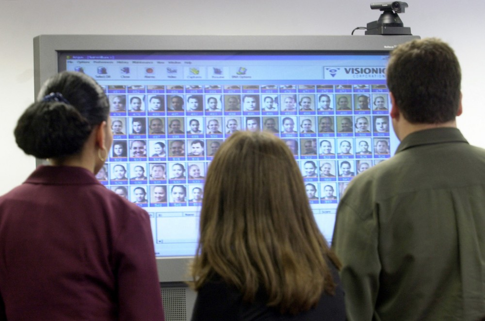 Employees of Visionics Corp., a top maker of fingerprint and facial recognition technology based in Jersey City, N.J., look at a large video monitor filled with images of their faces at the company's office  Wednesday, Oct. 3, 2001. Visionics has launched an advanced facial recognition system that can link any number of security cameras at an airport, for example, with a monitoring station. Workers are alerted in seconds if a camera picks up the face of a known terrorist or wanted felon in a crowd. (APPhoto/Mike Derer)
