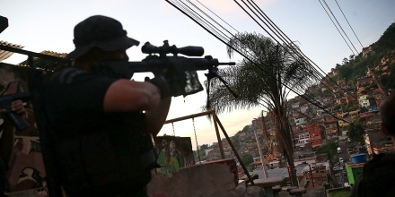 RIO DE JANEIRO, BRAZIL - MAY 13:  An officer from the CORE police special forces aims his weapon during an operation to search for fugitives in the Complexo do Alemao pacified community, or 'favela' on May 13, 2014 in Rio de Janeiro, Brazil. Ahead of the 2014 FIFA World Cup, Rio has seen an uptick in violence in its pacified slums. A total of around 1.6 million Rio residents live in shantytowns, many of which are controlled by drug traffickers.  (Photo by Mario Tama/Getty Images)