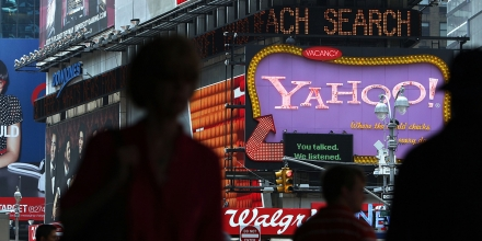 NEW YORK - JULY 29:  Pedestrians walk by a Yahoo sign in Times Square on July 29, 2009 in New York City. Taking aim at Google?s dominance, technology companies Microsoft and Yahoo announced Wednesday that they have reached a 10 year internet search partnership.  (Photo by Spencer Platt/Getty Images)