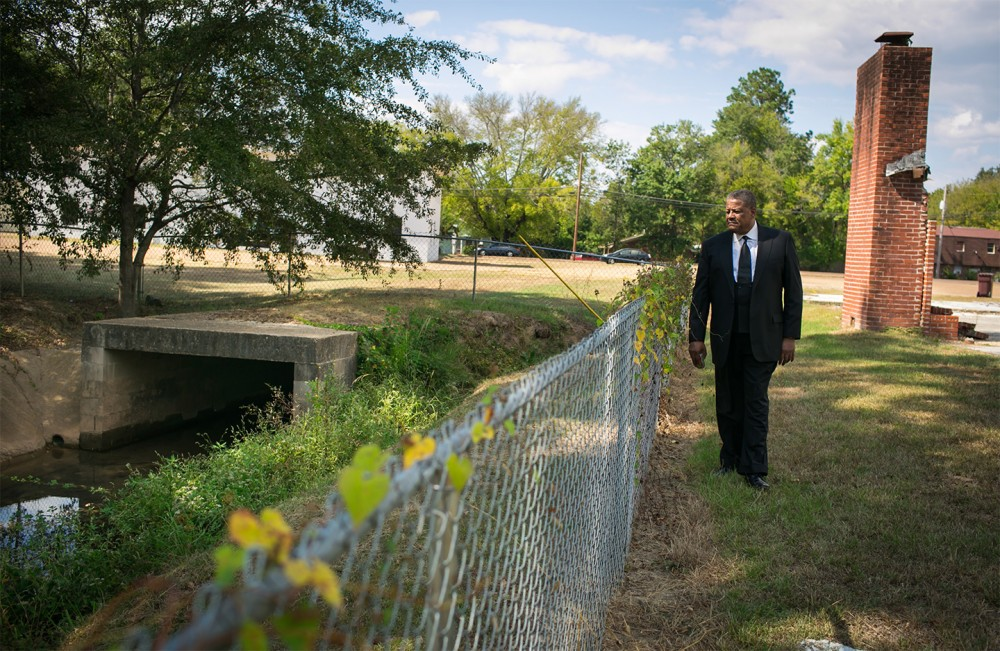 Reverend Steve Jamison walks alongside a polluted ditch that flows through the property of Maranatha Faith Center in Columbus, Mississippi. The ditch is where Reverend Jamison first discovered creosote on the land flushed out from the old Kerr McGee site.