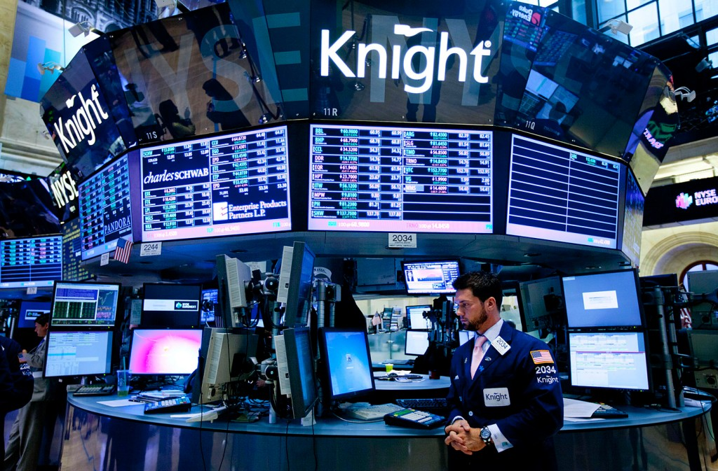 A trader works at the Knight Capital Group Inc. booth on the floor of the New York Stock Exchange (NYSE) in New York, U.S., on Tuesday, Aug. 7, 2012. U.S. stocks advanced, sending the Standard & Poor?s 500 Index higher for a third straight day, amid better-than-estimated corporate earnings and speculation global central banks will take steps to boost economic growth. Photographer: Jin Lee/Bloomberg via Getty Images