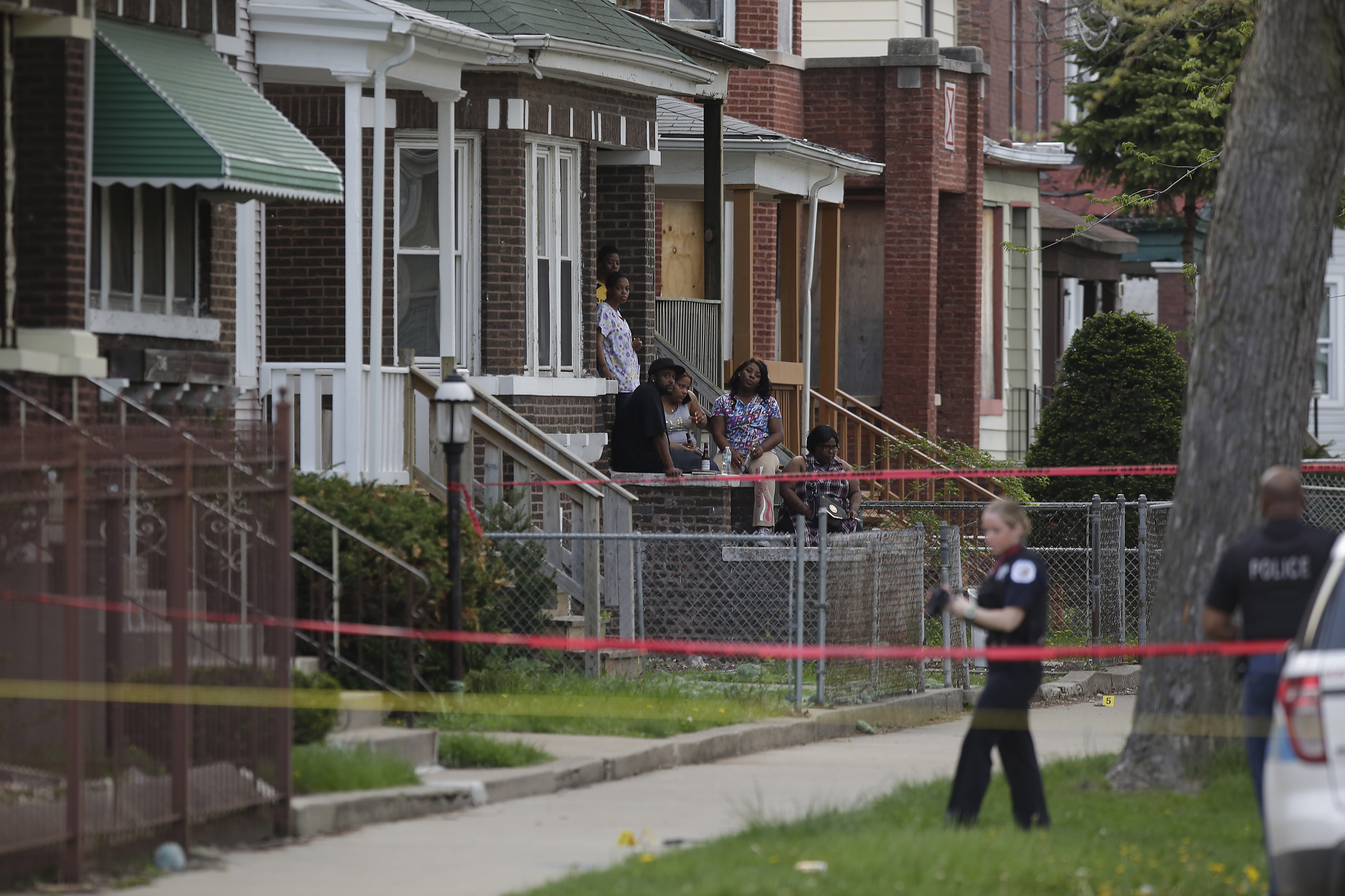 CHICAGO, IL - APRIL 25: People sitting on the front steps of a home watch as a Chicago Police evidence technician investigates the scene where a 16-year-old boy was shot in the head and killed and another 18-year-old man was shot and wounded on the 7300 block of South Sangamon Street on April 25, 2016 in Chicago, Illinois. Last week Chicago reached over 1,000 people shot since the beginning of the year. (Photo by Joshua Lott/Getty Images)