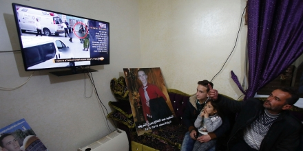 Yousri (R) the father of Abdul Fatah al-Sharif (portrait) watches on television the verdict of the trial of Israeli soldier Elor Azaria who killed their son, at their family home in the West Bank town of Hebron on January 4, 2017.Elor Azaria who shot dead Sharif as he lay wounded on the ground posing no apparent threat was convicted of manslaughter after a trial that deeply divided the country. / AFP / HAZEM BADER (Photo credit should read HAZEM BADER/AFP/Getty Images)