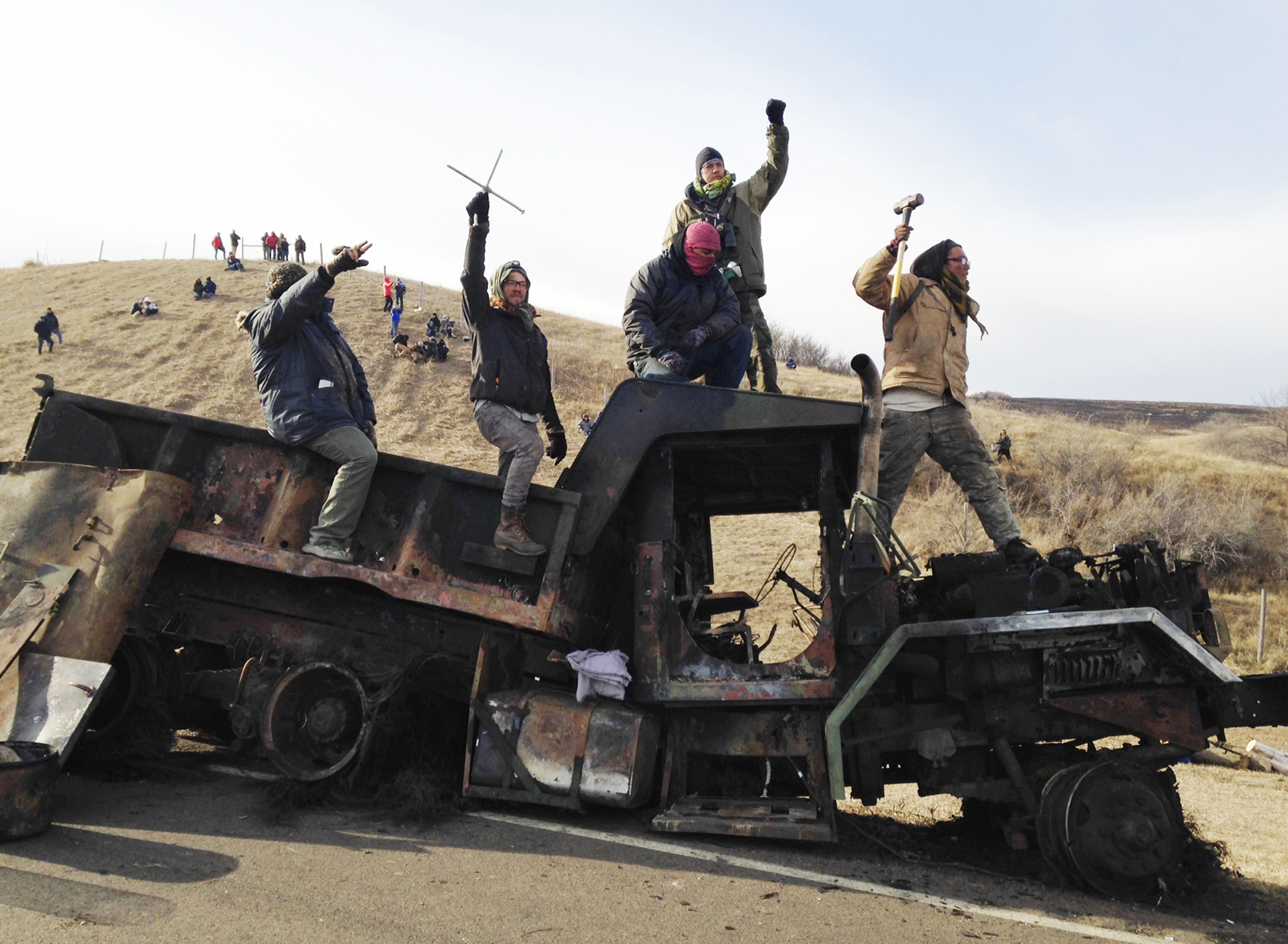 FILE - In this Monday, Nov. 21, 2016, file photo, protesters against the Dakota Access oil pipeline stand on a burned-out truck near Cannon Ball, N.D., that they removed from a long-closed bridge a day earlier on a state highway near their camp in southern North Dakota. President-elect Donald Trump holds stock in the company building the disputed Dakota Access oil pipeline, and pipeline opponents warn that Trump's investments could undercut any decision he makes on the $3.8 billion project as president. (AP Photo/James MacPherson, File)