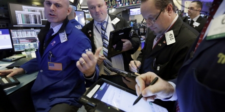 Specialist Mark Fitzgerald, left, works with traders at his post on the floor of the New York Stock Exchange, Tuesday, Jan. 10, 2017. The stock market is getting off to a mixed start as drops in real estate and utilities offset gains in other sectors including health care. (AP Photo/Richard Drew)