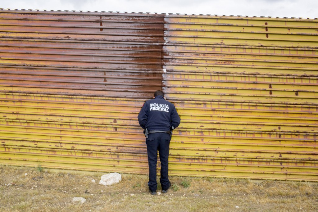 TIJUANA, MX. - APRIL 8 2016:  Mexican Federal Policeman escort a tour of the border wall near Tijuana. </p><br /><br /><br /><br /><br /> <p>Natalie Keyssar