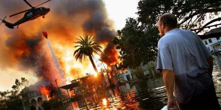 UNITED STATES - SEPTEMBER 04:  A man watches a house burn on Napolean St. as helicopters try to extinguish the fire by dropping water from above in Hurricane Katrina ravaged New Orleans. Because of the extensive flooding caused by the breaking of the city's levies, fire trucks were unable to reach burning homes and in some cases whole blocks burned to the ground.  (Photo by Craig Warga/NY Daily News Archive via Getty Images)