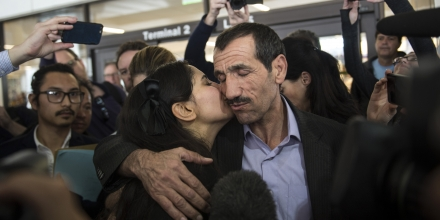 Marjan K. Vayghan, left, gives a kiss to her uncle Ali Vayeghan as he arrives at the international terminal at Los Angeles International Airport in Los Angeles on Thursday, Feb. 2, 2017. Vayeghan, who had been turned away from the airport under President Donald Trump's executive order barring immigrants from seven Muslim-majority nations, returned Thursday to an emotional welcome from family members who greeted him with California-grown flowers and well-wishers who sang