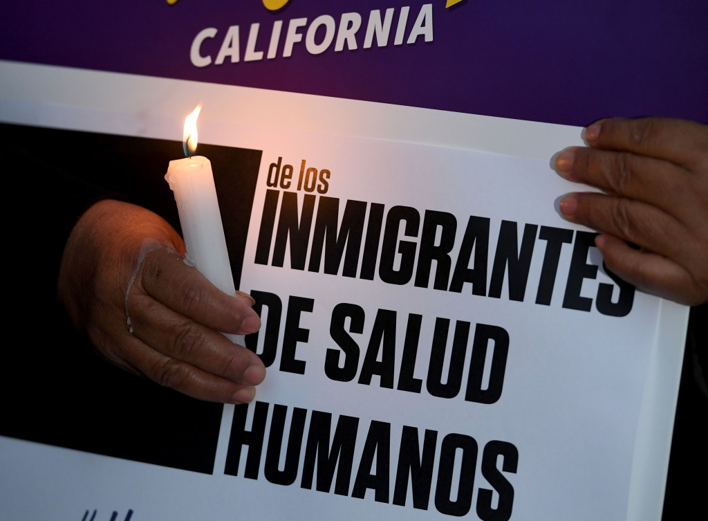 "Migrant rights groups hold candles during a vigil to protest against US President Donald Trump's new crackdown on ""sanctuary cities"", outside the City Hall in Los Angeles on January 25, 2017.Some 300 such cities, counties or states -- from New York to Los Angeles -- exist throughout the United States, and many of them have vowed since Trump's election to protect the estimated 11 million undocumented migrants living in the country. / AFP / Mark RALSTON (Photo credit should read MARK RALSTON/AFP/Getty Images)"