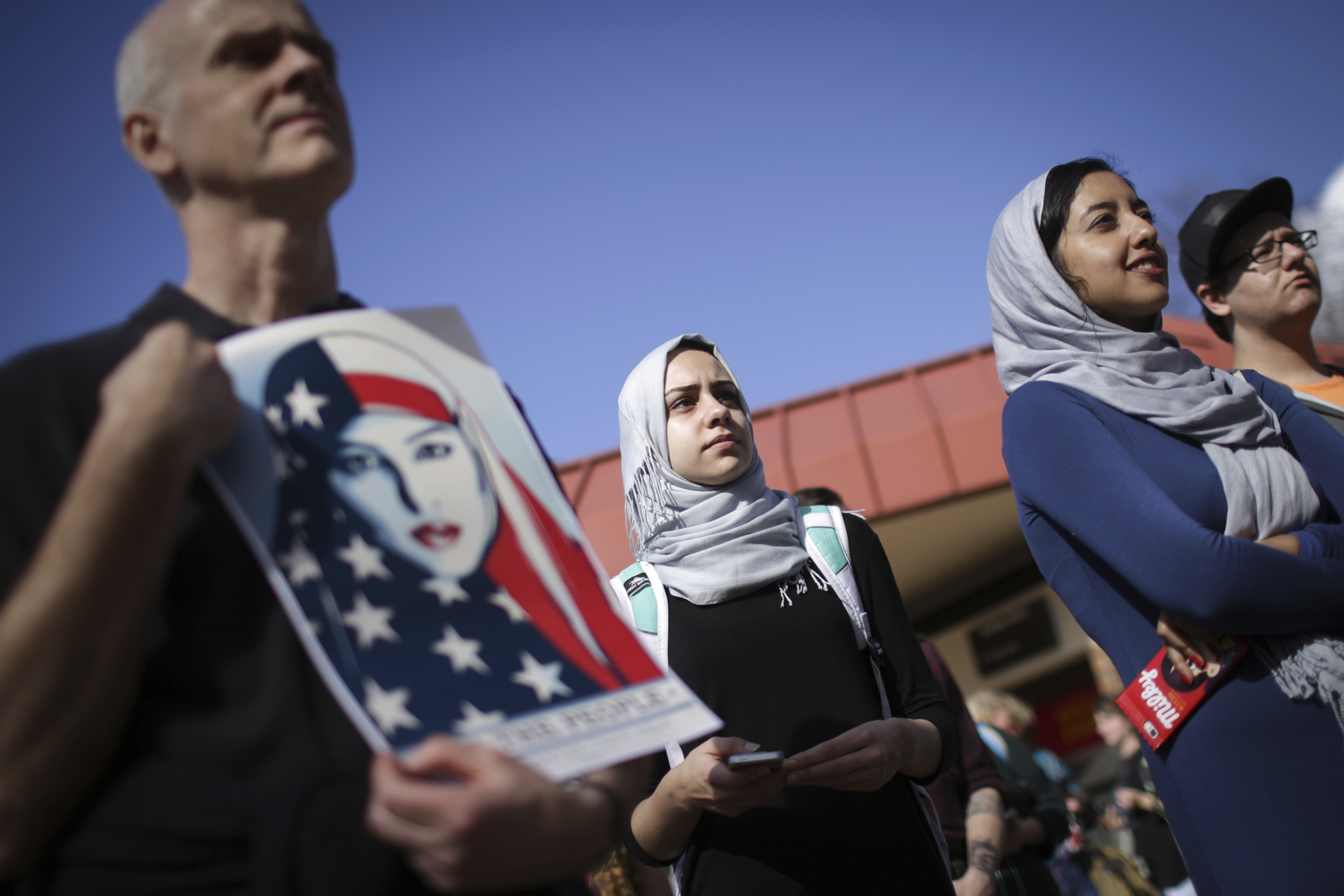 """Mae Eldahshoury, center, looks on as speakers voice concerns about President Trump's policies and potentially discriminatory practices at the University of Georgia, Friday, January 20, 2017. Eldahshoury, of the Muslim Student Alliance, came to the rally because of """"Trump's rhetoric to ban muslims"""" and show support for everyone that may feel afraid. (John Roark/Athens Banner-Herald via AP)"""