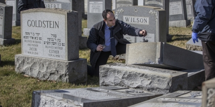 Northeast Philadelphia Police Detective Timothy McIntyre, center, dusts for fingerprints on one of the headstones that were vandalized at Mount Carmel Cemetery in Philadelphia on Sunday, Feb. 26, 2017. More than 100 headstones have been vandalized at the Jewish cemetery in Philadelphia, damage discovered less than a week after similar vandalism in Missouri, authorities said. (Michael Bryant/The Philadelphia Inquirer via AP)