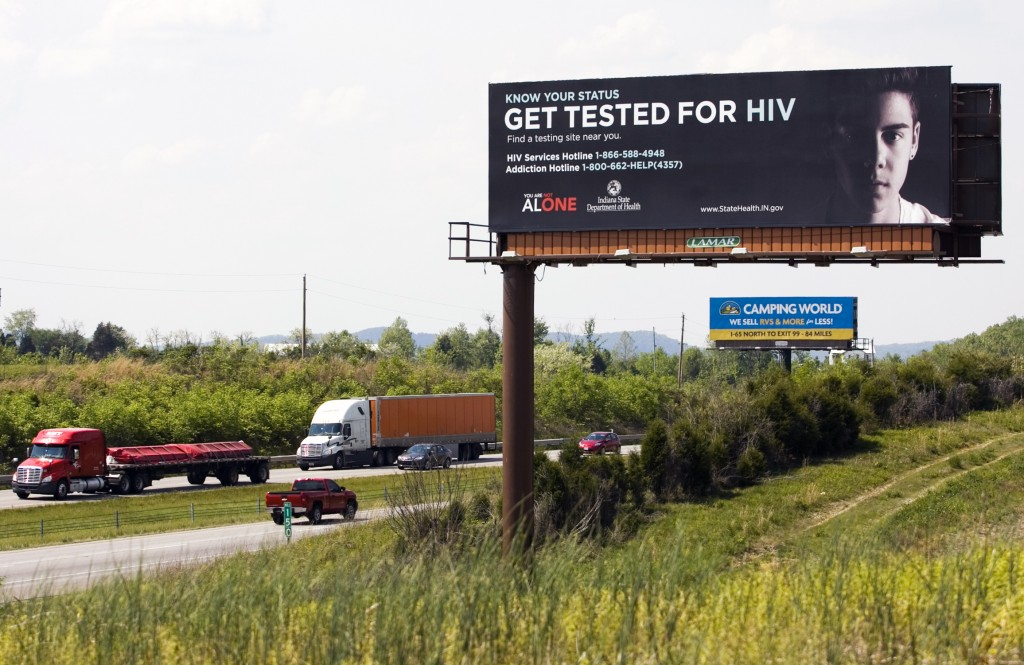 "Traffic moves along Interstate 65 near Memphis past an HIV awareness billboard, which is part of the ""You Are Not Alone"" campaign started by the state health department to raise awareness among truck drivers and travelers about the Scott County HIV epidemic. After months of mounting HIV cases, rural Scott County, that's facing Indiana's worst-ever HIV outbreak, is seeing a dwindling number of new infections, possibly signaling that the outbreak is winding down, a state health official said Thursday, May 7, 2015 (Christopher Fryer/News and Tribune via AP)"