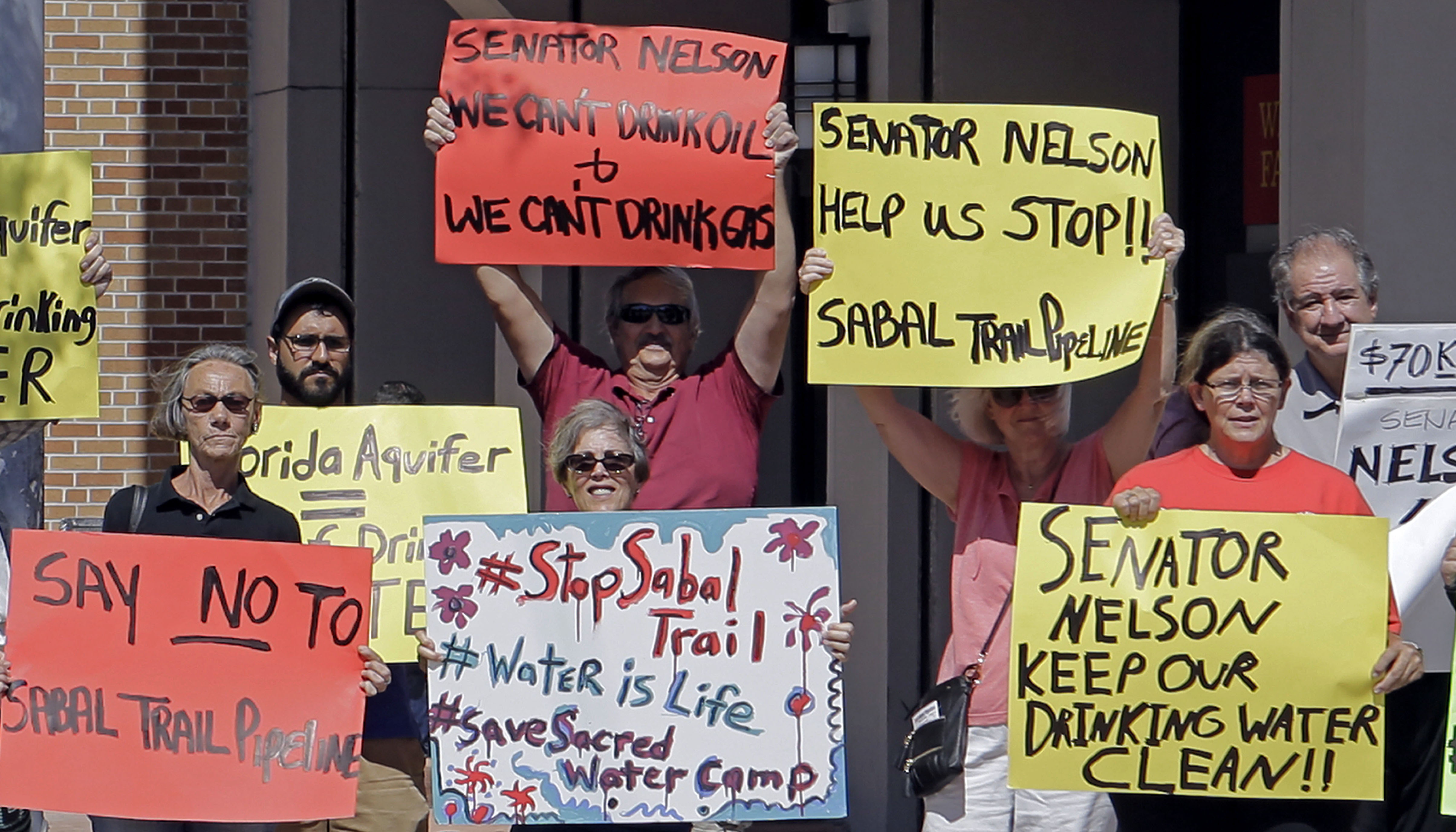 Community activists hold signs as they protest the Sabal Trail pipeline, in front of the office of U.S. Sen. Bill Nelson, Tuesday, Feb. 14, 2017, in Coral Gables, Fla. The Sabal Trail is an underground natural gas pipeline project that originates in Alabama, stretches through Georgia and terminates in Florida. (AP Photo/Alan Diaz)
