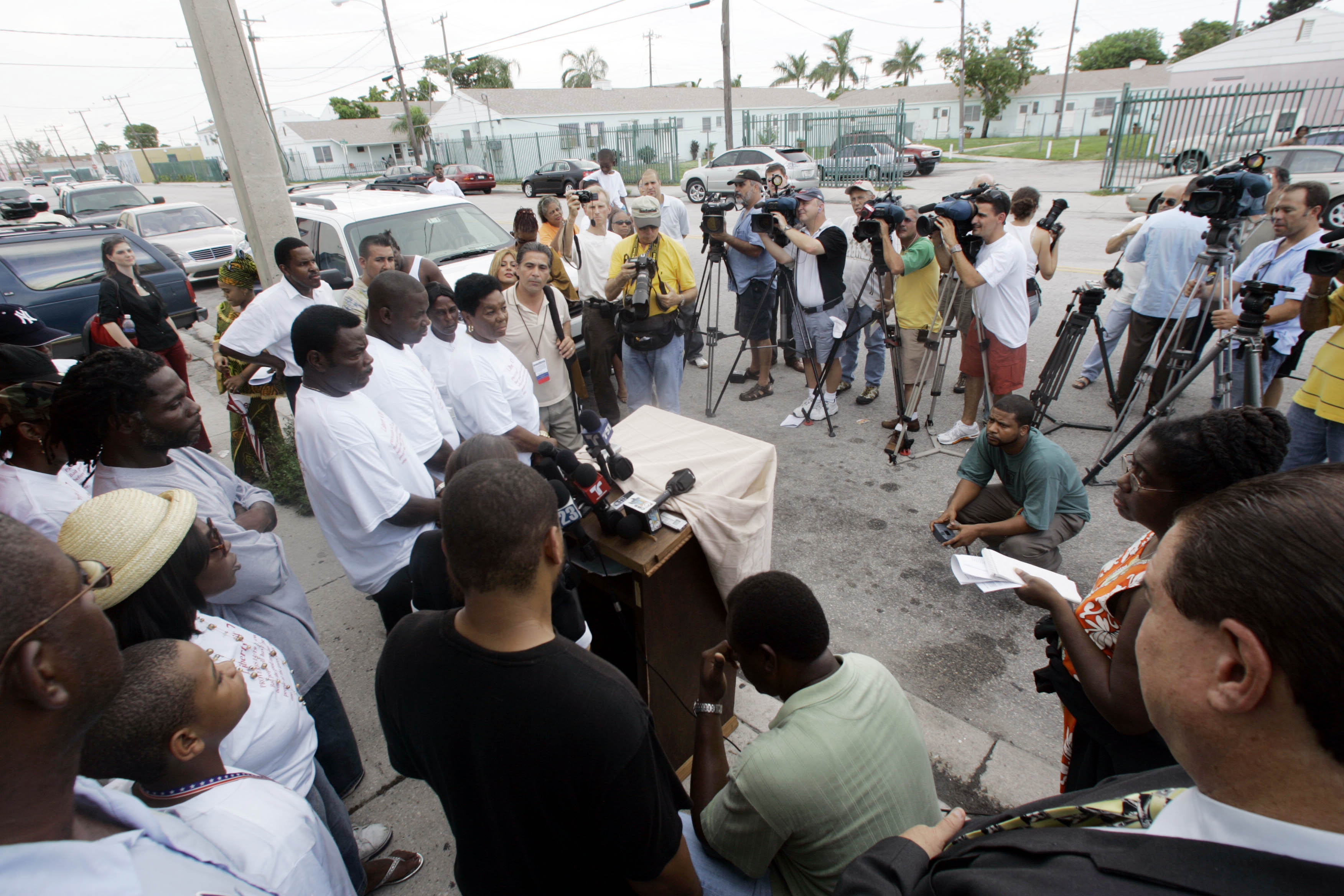 Family members of some of the seven men charged with plotting to destroy the Sears Tower in Chicago and other buildings, center left in white t-shirts,  look on during a news conference where activists spoke, Thursday, June 29, 2006 at the Liberty City neighborhood warehouse in Miami where the FBI arrested most of the men.  (AP Photo/Wilfredo Lee)