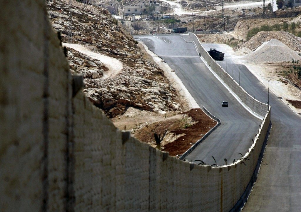 A car drives on a new segment of a highway separating Palestinian and Israeli traffic near the West Bank city of Ramallah, 12 August 2007. Once finished, the highway will connect north of the West Bank to its south, bypassing Jerusalem. The highway will be used by both Palestinians and Israelis, but on two different lanes separated by a wall of concrete. AFP PHOTO/ABBAS MOMANI (Photo credit should read ABBAS MOMANI/AFP/Getty Images)