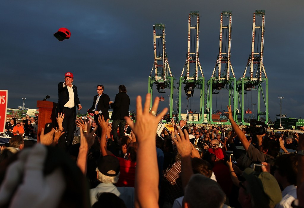 LOS ANGELES, CA - SEPTEMBER 15:  Republican presidential candidate Donald Trump (L) throws a hat to supporters during a campaign rally aboard the USS Iowa on September 15, 2015 in Los Angeles, California. Donald Trump is campaigning in Los Angeles a day ahead of the CNN GOP debate that will be broadcast from the Ronald Reagan Presidential Library in Simi Valley.  (Photo by Justin Sullivan/Getty Images)