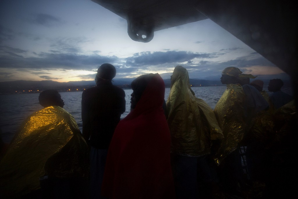 Wrapped in blankets, Sub-Saharan migrants stand on the deck of the Golfo Azzurro rescue vessel after arriving at the port of Messina, in Italy, with more than 299 migrants aboard the ship rescued by members of Proactive Open Arms NGO, on Sunday, Jan. 29, 2017. (AP Photo/Emilio Morenatti)