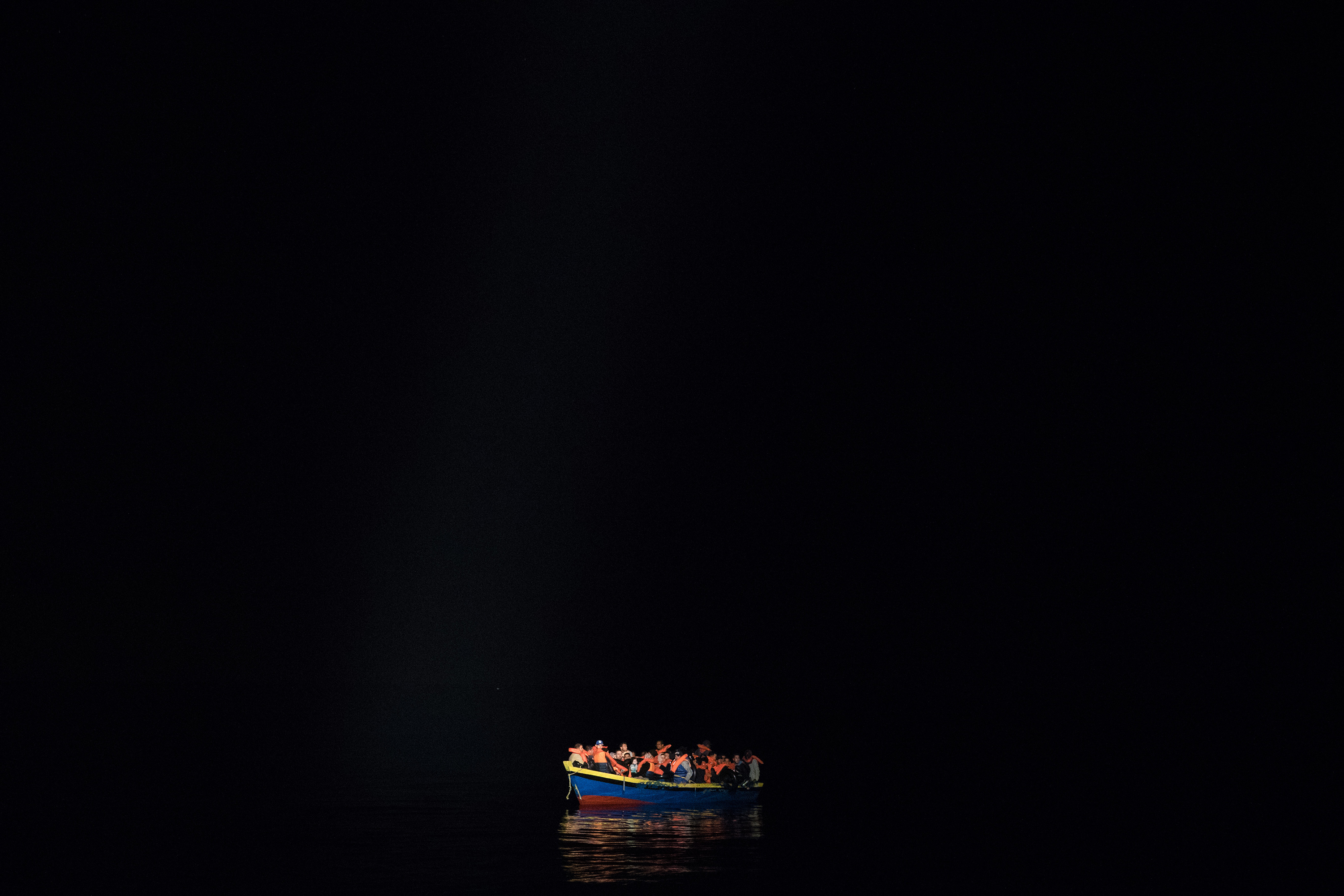 POZZOLLO, ITALY - NOVEMBER 22:  A wooden boat carrying refugees and migrants waits to be escorted to the Topaz Responder as members of MOAS, Migrant Offshore Aid Station make rescues at sea on November 22nd, 2016 in Pozzollo, Italy. The MOAS team worked through the night and into the next morning rescuing 'approximately' 600 people from vessels though that figure could change. MOAS are currently patrolling international waters off the coast of Libya, and running rescue missions for the many migrants and refugees who continue to attempt to make the dangerous crossing across the Mediterranean Sea to Italy. MOAS are a Malta based registered foundation dedicated to providing professional search-and-rescue assistance to refugees and migrants in distress at sea and work alongside with the Red Cross on board the Topaz Responder. The number of deaths this year of people crossing the Mediterranean has risen to almost 4,300. MOAS alone have rescued around 19,000.  (Photo by Dan Kitwood/Getty Images)