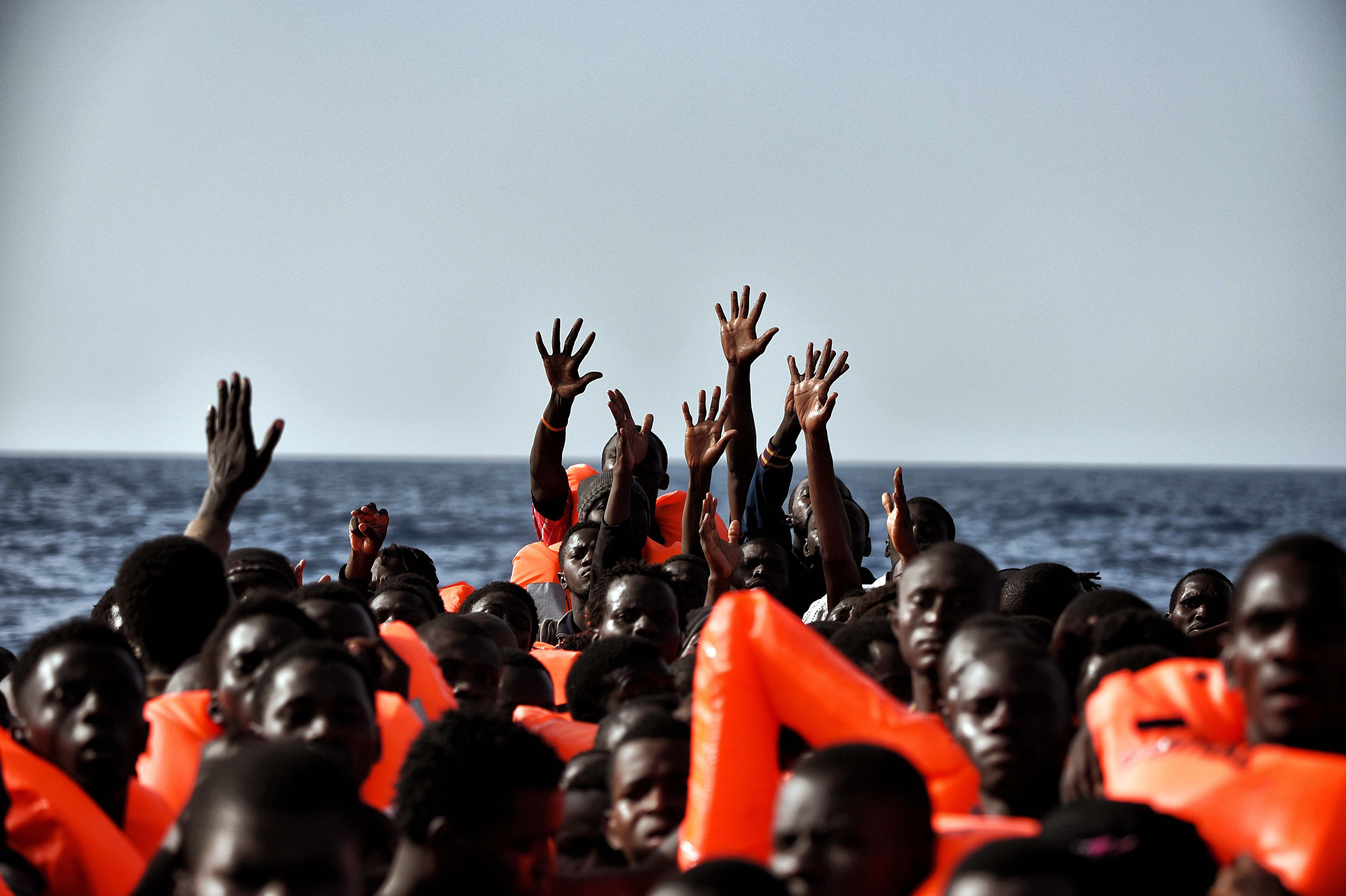 TOPSHOT - Migrants wait to be rescued as they drift in the Mediterranean Sea some 20 nautical miles north off the coast of Libya on October 3, 2016. Italy coordinated the rescue of more than 5,600 migrants off Libya, three years to the day after 366 people died in a sinking that first alerted the world to the Mediterranean migrant crisis. / AFP / ARIS MESSINIS (Photo credit should read ARIS MESSINIS/AFP/Getty Images)