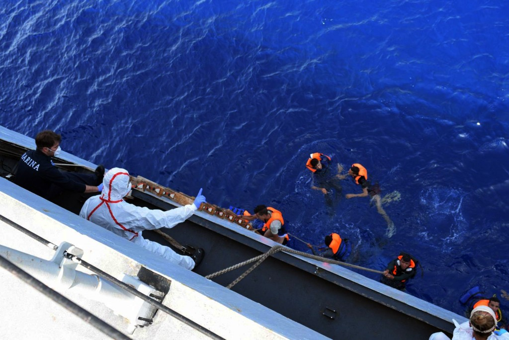 SICILIAN STRAIT, MEDITERRANEAN SEA - MAY 25: Italian marines rescue migrants from a capsized boat at Sicilian Strait, between Libya and Italy, in Mediterranean sea on May 25, 2016. The Italian Navy saved around 500 migrants as they found dead bodies of seven migrants in the sea during the operations. (Photo by Italian Navy / Marina Militare/Anadolu Agency/Getty Images)