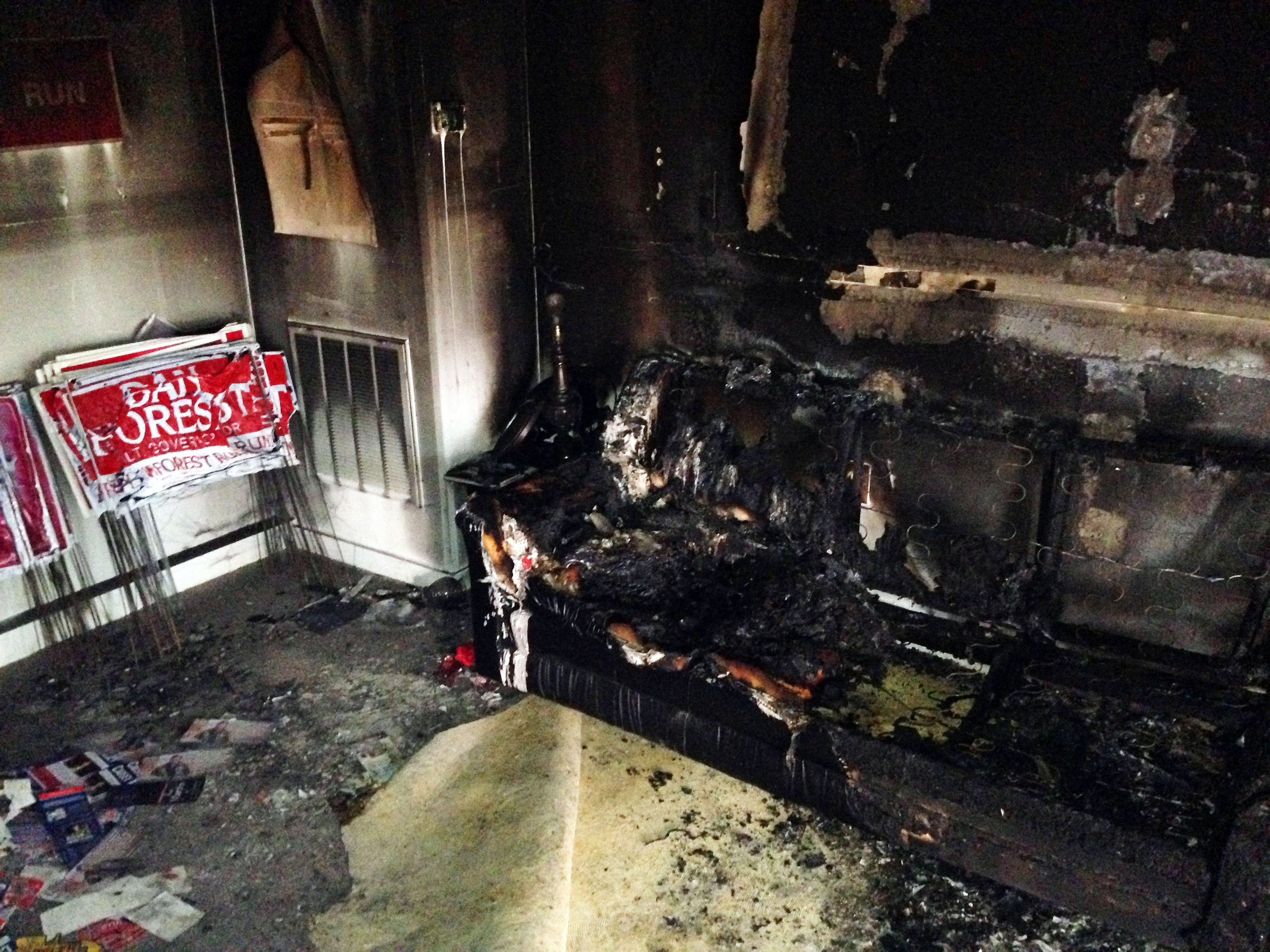 "A burned couch is shown next to warped campaign signs at the Orange County Republican Headquarters in Hillsborough, NC on Sunday, Oct. 16 2016. Someone threw flammable liquid inside a bottle through a window overnight and someone spray-painted an anti-GOP slogan referring to ""Nazi Republicans"" on a nearby wall, authorities said Sunday. State GOP director Dallas Woodhouse said no one was injured. (AP Photo/Jonathan Drew)"