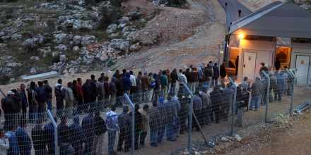 NI'ILIN, WEST BANK - JANUARY 03:  Palestinian labourers line up to cross an Israeli checkpoint as they return to their homes after a day's work in the Jewish state on January 3, 2010 near the village of Ni'ilin in the West Bank. Palestinians complain that the thousands of workers who have been granted coveted Israeli work permits find themselves waiting for hours without shelter and in all kinds of weather to cross the military checkpoints, leaving home hours before sunrise and returning late in the evening because of delays at the crossings.  (Photo by David Silverman/Getty Images)
